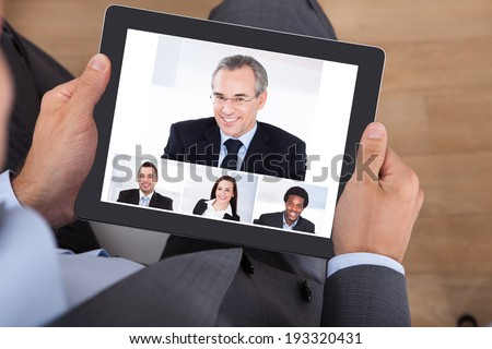 High angle view of businessman video conferencing with coworkers on digital tablet in office - stock photo