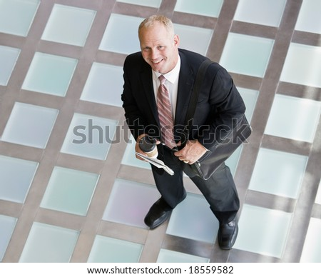 High angle view of businessman with briefcase and coffee in the morning - stock photo