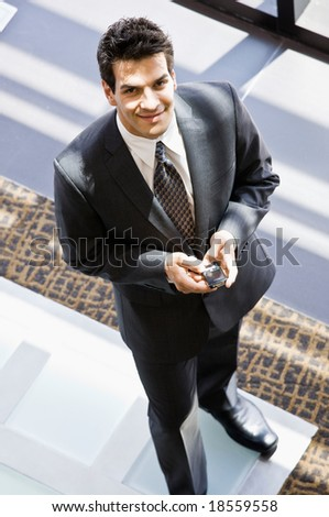 High angle view of businessman with cell phone text messaging  in office lobby