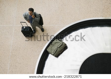 High angle view of businessman with luggage - stock photo