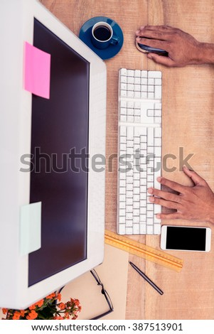 High angle view of businessman working on computer at desk in office - stock photo