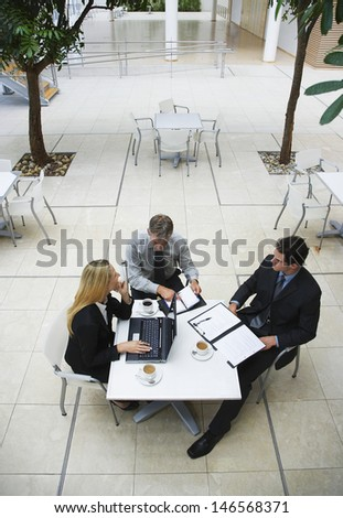 High angle view of businessmen and businesswoman having a discussion at office cafe - stock photo