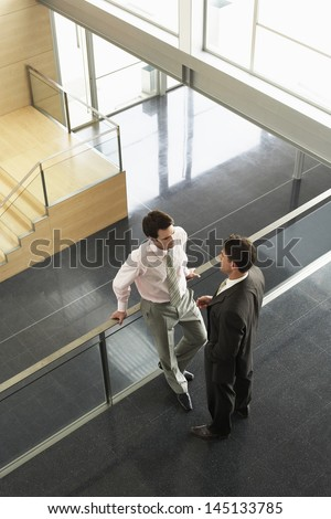 High angle view of businessmen conversing while standing by railing in office