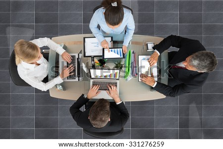 High Angle View Of Businesspeople Analyzing Graphs On Electronic Devices In Office - stock photo