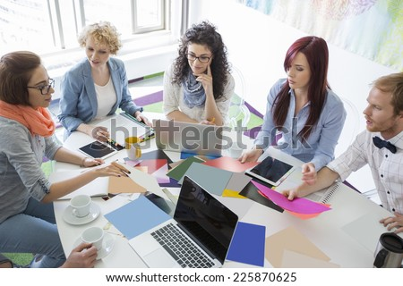 High angle view of businesspeople analyzing photographs in creative office - stock photo