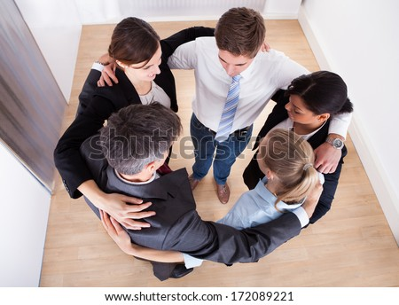 High Angle View Of Businesspeople Making Huddle - stock photo