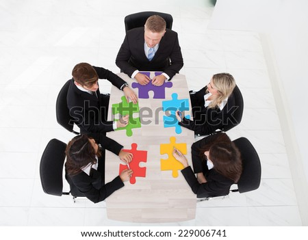 High angle view of businesspeople with jigsaw pieces sitting at table in office - stock photo