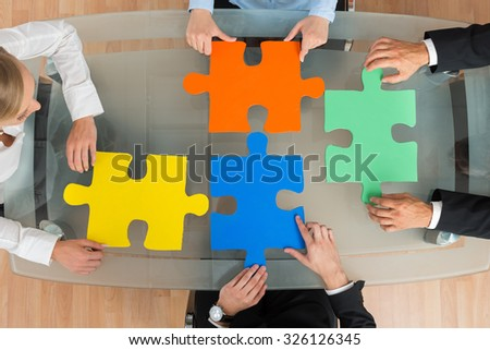 High Angle View Of Businesspeople With Multi-colored Jigsaw Pieces At Desk - stock photo