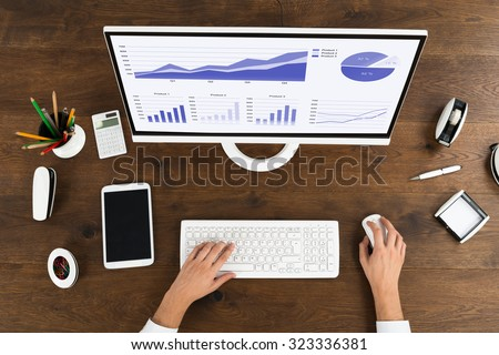 High Angle View Of Businessperson Analyzing Statistical Graph On Computer At Wooden Desk - stock photo