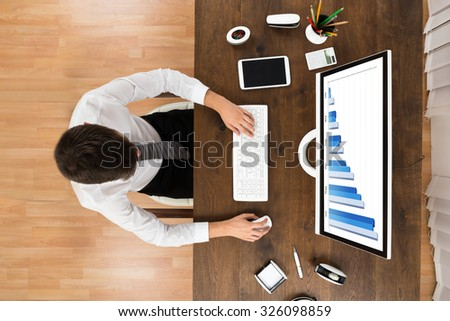 High Angle View Of Businessperson Analyzing Statistical Graph On Computer At Wooden Desk