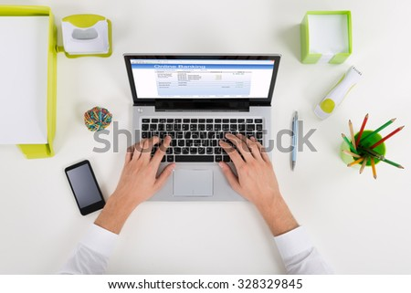 High Angle View Of Businessperson Banking Online On Laptop At Desk - stock photo