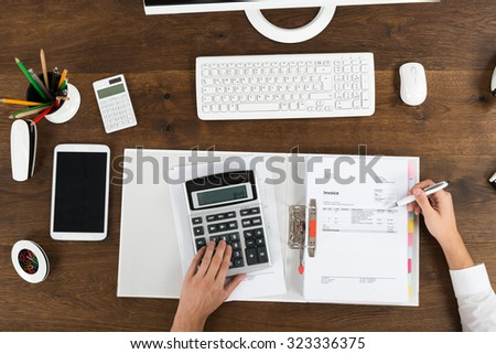 High Angle View Of Businessperson Calculating Tax At Wooden Desk - stock photo