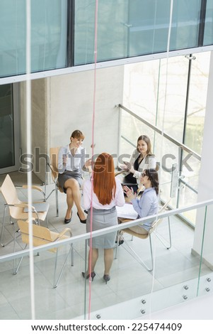 High angle view of businesswoman giving presentation to colleagues in office - stock photo