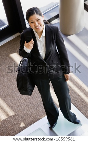 High angle view of businesswoman holding briefcase in office lobby - stock photo