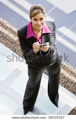 High angle view of businesswoman holding electronic organizer in office lobby - stock photo