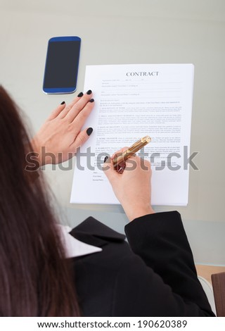 High angle view of businesswoman signing contract papers at desk in office - stock photo