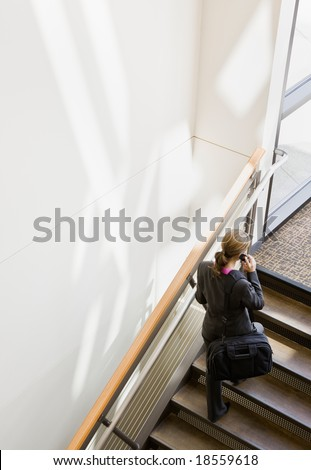 High angle view of businesswoman with briefcase talking on cell phone and ascending stairs - stock photo
