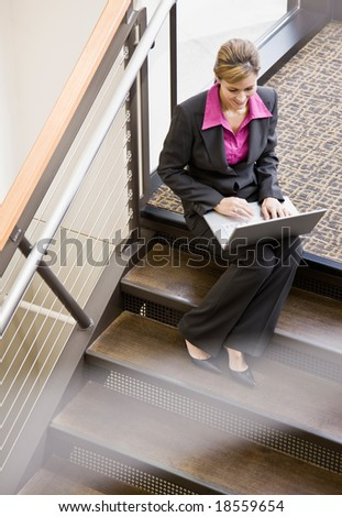High angle view of businesswoman working on laptop on office stair landing - stock photo