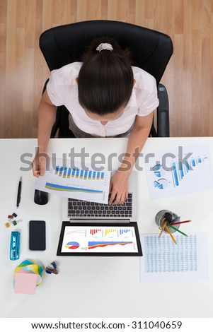 High Angle View Of Businesswoman Working With Graphs At Desk - stock photo