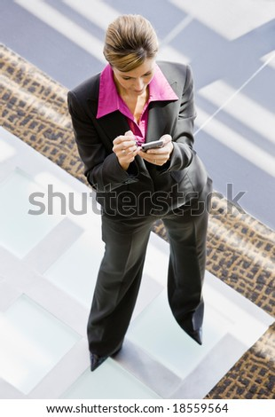High angle view of businesswoman writing in electronic organizer in office lobby - stock photo