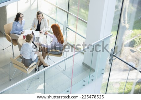 High angle view of businesswomen discussing at table in office - stock photo