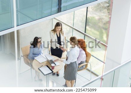 High angle view of businesswomen shaking hands at table in office - stock photo