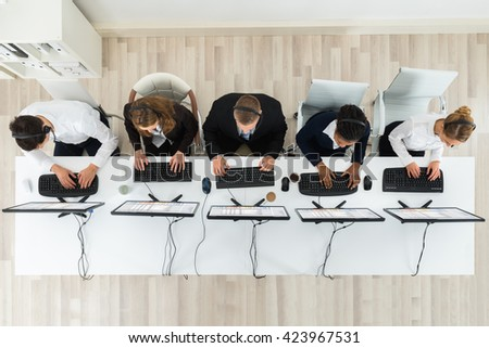 High Angle View Of Call Center Operators Working On Computers In Office - stock photo