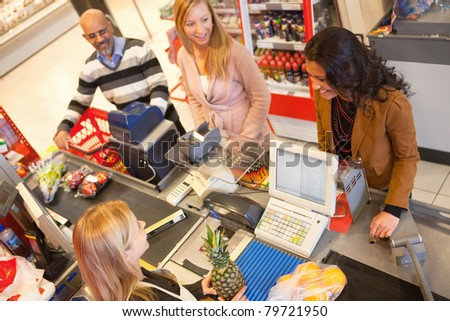 High angle view of cashier with a line of people at the check-out counter - stock photo