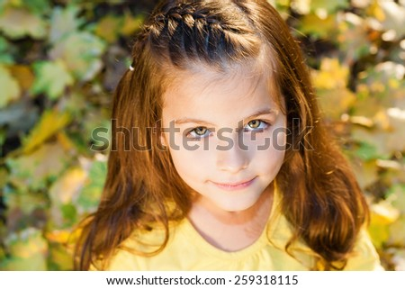 High angle view of cheerful little girl looking at camera.Autumn colorful park, shallow doff, sunset light, lens flare - stock photo