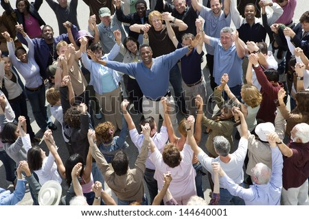 High angle view of cheerful man standing amidst people with hands raised - stock photo