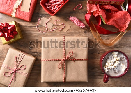 High angle view of Christmas presents and hot chocolate on a wood table. Plain wrapped gifts with string, candy canes and ribbon. - stock photo