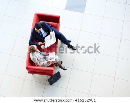 High angle view of colleagues sitting on sofa and talking - stock photo