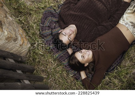 High angle view of couple lying on a blanket in grass - stock photo