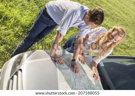 High angle view of couple reading map on car hood during road trip - stock photo