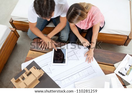 High angle view of couple using tablet PC with blueprint and model structure on table - stock photo