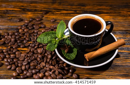 High Angle View of Cup of Hot Black Coffee Served in Black Cup and Saucer with Fresh Mint and Cinnamon Stick on Wooden Table Scattered with Roasted Beans - stock photo