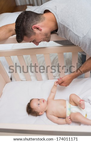 High angle view of cute baby boy looking at father in bedroom - stock photo