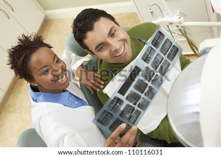 High angle view of dentist showing male patient tooth x-ray - stock photo