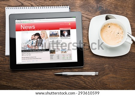 High Angle View Of Digital Tablet With Business News On Screen - stock photo