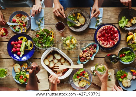 High angle view of dining table with people sitting and eating - stock photo