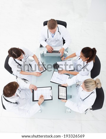 High angle view of doctors analyzing medical reports at desk in clinic - stock photo