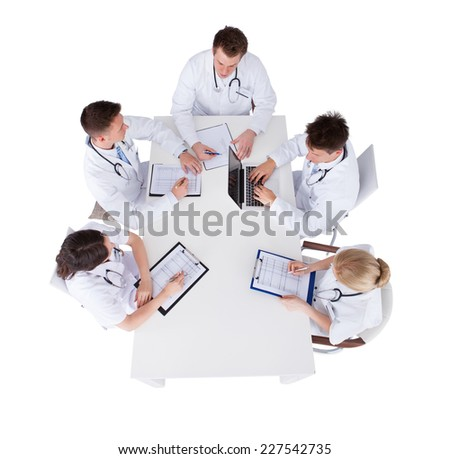 High angle view of doctors with medical charts and laptop discussing at table over white background - stock photo