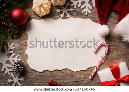 High angle view of empty letter on wooden table with christmas decoration. Top view of empty xmas wish list with little gift present and santa claus hat on wooden background.
