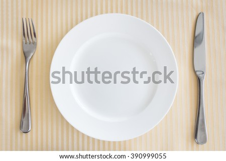 High angle view of empty plate with fork and table knife.