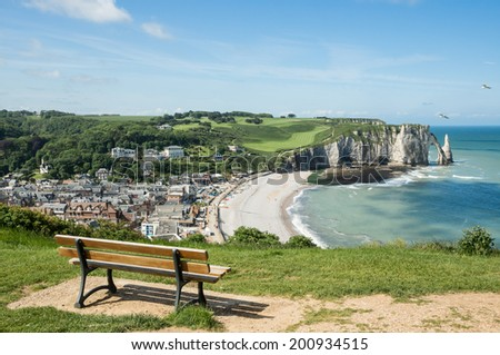 High angle view of Etretat Aval cliff with a chair on the foreground, rocks and natural arch landmark and blue ocean. Normandy, France, Europe. - stock photo