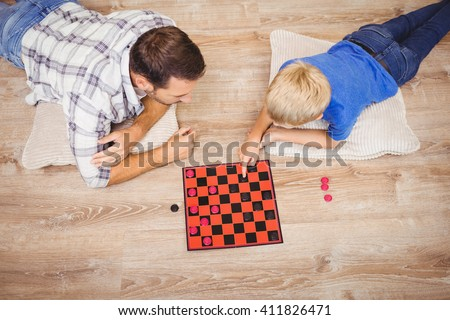 High angle view of father and son playing checker game while lying on floor at home - stock photo