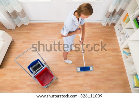 High Angle View Of Female Cleaner Cleaning Floor With Mop