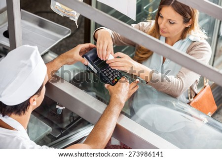 High angle view of female customer paying through smartphone at butcher's shop - stock photo