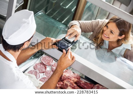High angle view of female customer paying through smartphone at butchery - stock photo