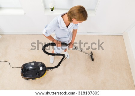 High Angle View Of Female Maid Using Vacuum Cleaner For Cleaning Floor - stock photo